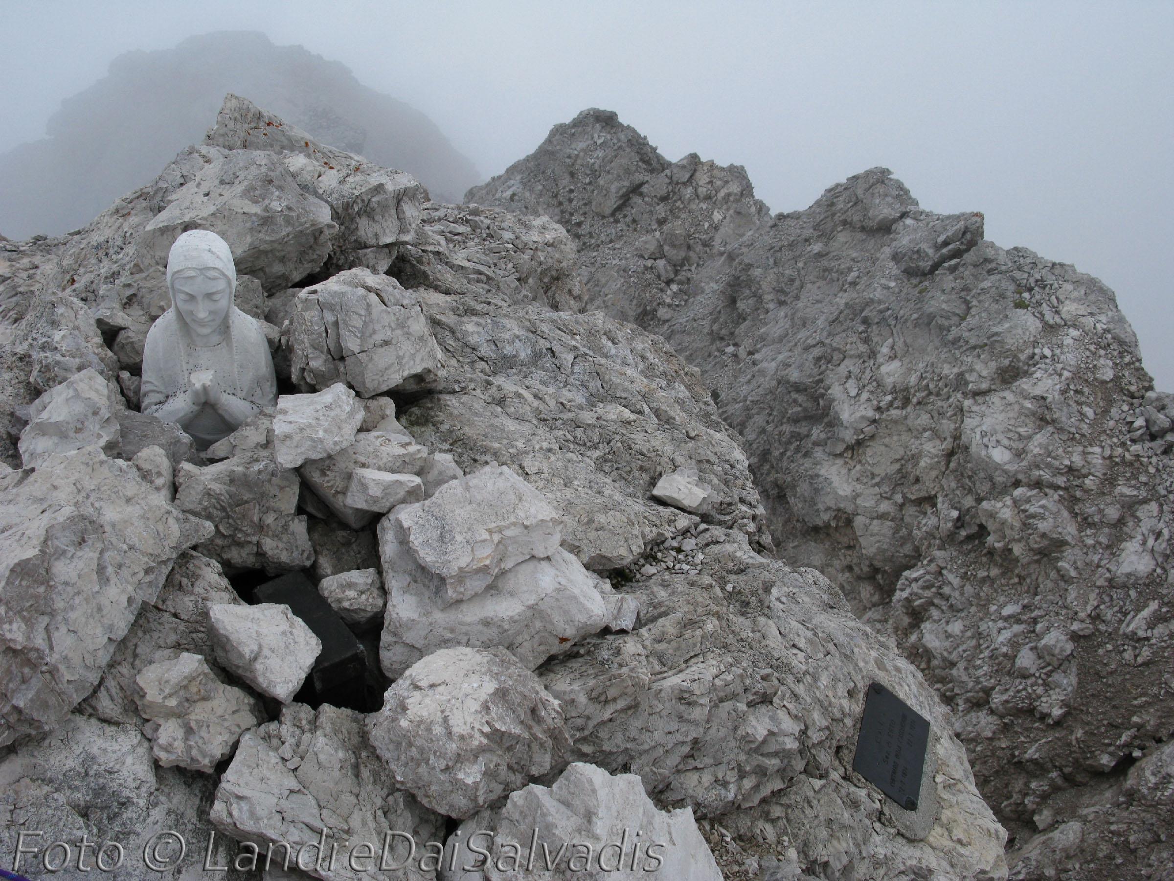 In cima: madonnina in pietra, cassetta col libro di vetta e targa.